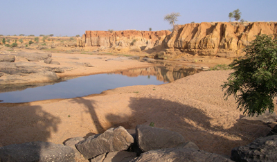 Immediately downstream from The Confluence, contact with the protohistoric terrace (at the top) is reflected by a terrace edge of 10 m, which evidences the strength of the recent incision. To the left in the background, the Oumounaama sector, more open and developed in the Pleistocene formations. Photo M. Rasse