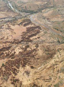 Sur cette photo prise vers l'amont, les ravinements d'Ounjougou sont très reconnaissables dans le secteur de la confluence. On peut également distinguer la terrasse protohistorique (qui domine directement le Yamé) du glacis supérieur (au premier plan à gauche). Photo aérienne D. Gladsteen