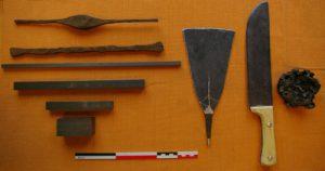 Les matériaux des essais de forgeage traditionnel au pays dogon (Janvier 2008). À gauche : les différentes sortes de fer utilisées : barres anciennes de fer, barres modernes de différentes sections. Au centre : une lame de houe et un grand couteau. À droite : une scorie de forge . Photo R. Soulignac